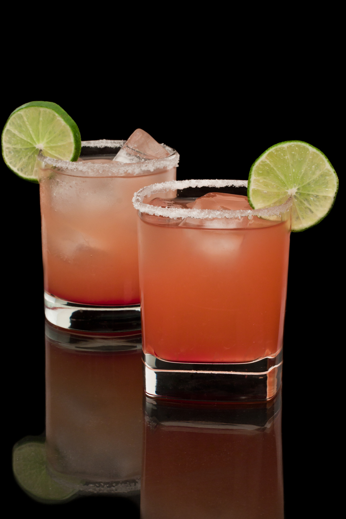 Pink and red drinks on a reflective surface with a salt rim and a lime garnish