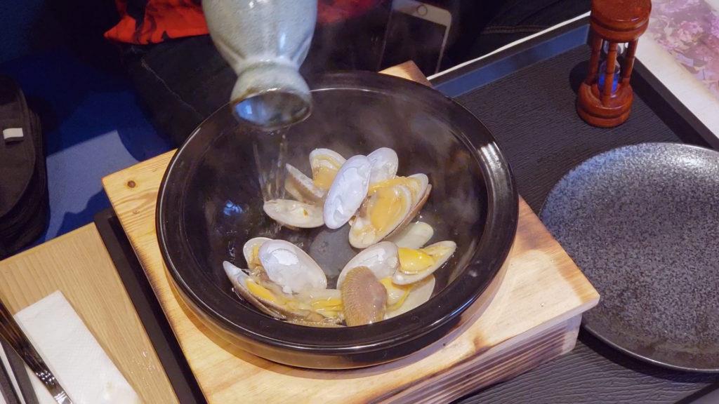天然火山石清酒煮花蛤(時令) 「高溫熱石燒煮方式」為DOMON居酒屋自家特色的烹調方式。火山石經高溫燒熱後置於鍋底,再注入北海道國士無雙清酒與花蛤同時蒸焗。清酒遇熱後迅速蒸發,散發濃郁酒香,更能提昇花蛤獨特鮮味。